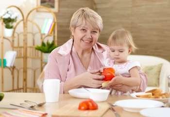 Бабушка кормит маленькую внучку